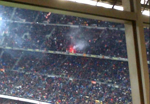 Torcedores do Real Madrid jogam sinalizador na torcida do Barcelona