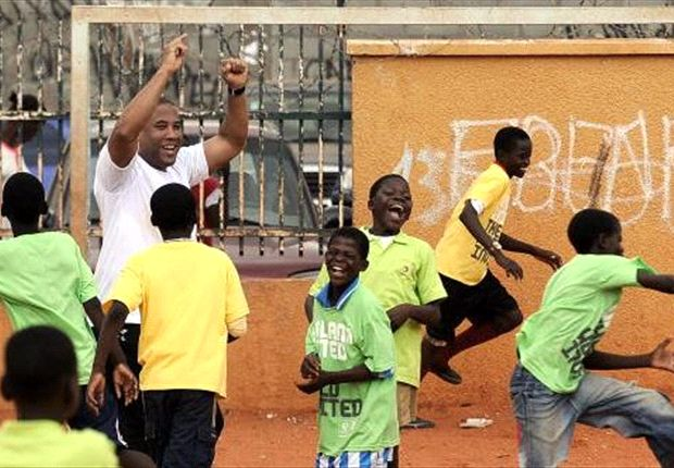Former Liverpool winger John Barnes plays with children at the Lar Kuzola orphanage in Luanda