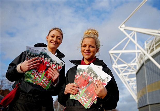 Saints supporters holding the matchday programmes.