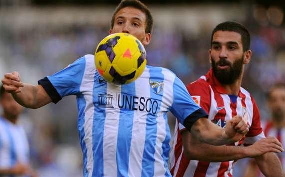 Malaga's Ignacio Camacho (L) and Atletico Madrid's Arda Turan