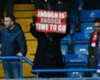 An Arsenal fan holds up a sign calling for Arsene Wenger's departure after a 3-1 loss to Chelsea