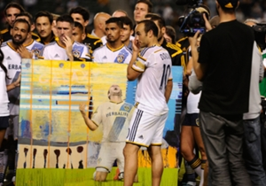 Landon Donovan is presented a painting after his final MLS regular season home game